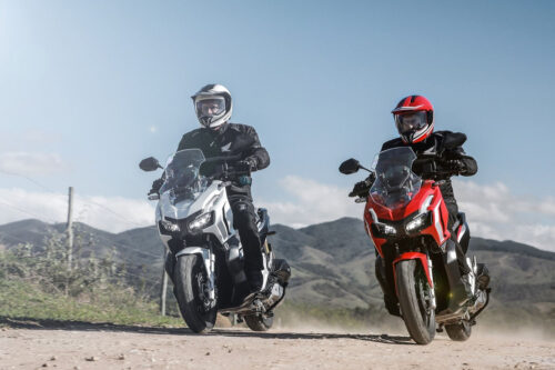 honda adv 150 nas cores vermelho e branco sendo pilotadas em estrada de terra com montanhas ao fundo